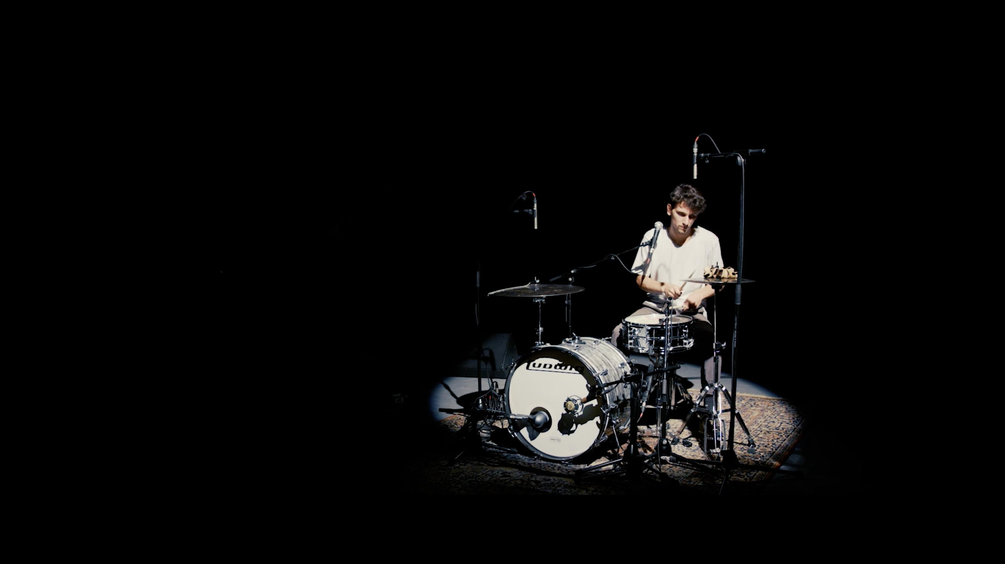 Leon Mucke spielt Schlagzeug in einem dunklen Raum